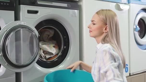 Öffentliche Selbstbedienungswäscherei. Eine junge hübsche Frau lädt schmutzige Wäsche in die Waschmaschine.