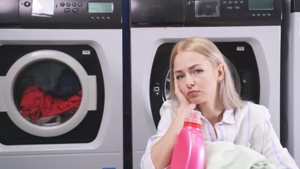 Egy gyönyörű szőke nő ül a mosógép mellett, és várja, hogy kimossák az alsóneműjét és a ruháit.