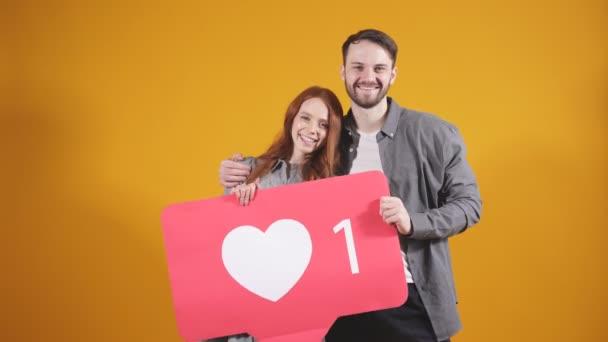 Mann und Frau haben ein soziales Netzwerk-Symbol, sie empfehlen, sich anzumelden und viele Likes auf einen interessanten Blog im Internet zu setzen, ein geschlossenes Studiobild auf orangefarbenem Hintergrund.