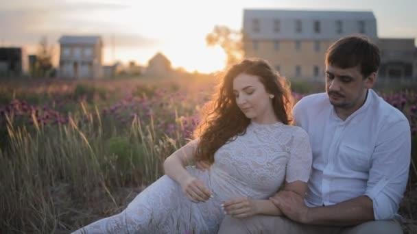 junges kaukasisches Paar sitzt auf dem Feld