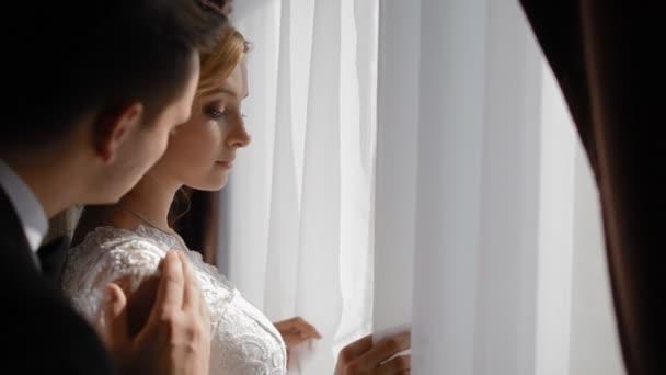 Menyasszony és a vőlegény állni az ablak mellett