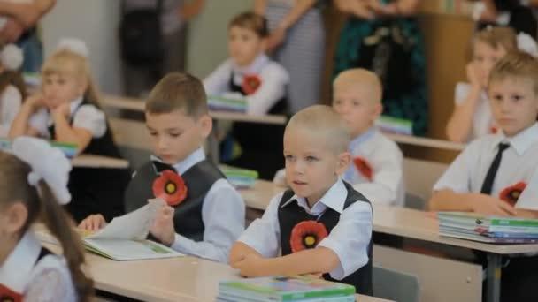 Dněpr, Ukrajina - 1. září 2015: První bývalých žáků v národní oblečení sedí u stolu v učebně.
