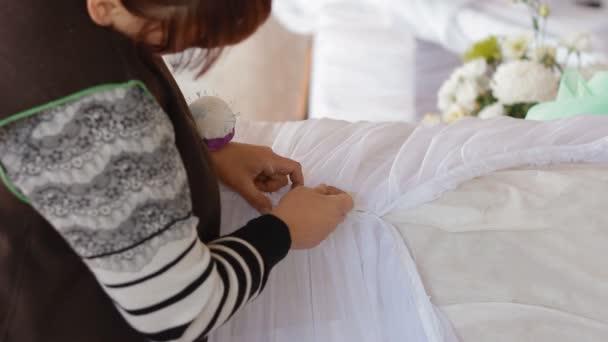 Frau drapiert Säule mit weißem Tuch