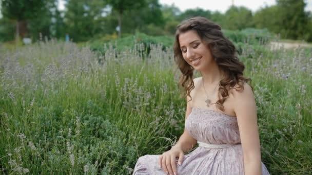Mladá žena v dlouhé fialové šaty sedí v levandule