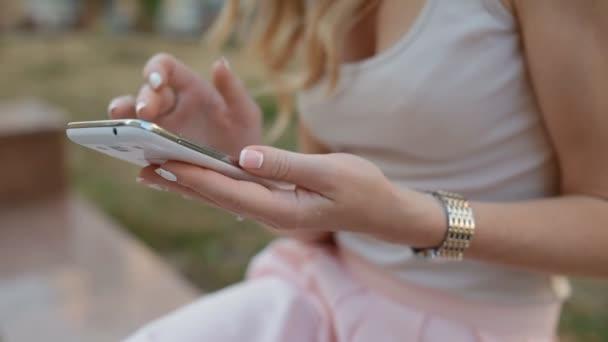 Junge blonde Frau benutzen Sie ihr Telefon im freien