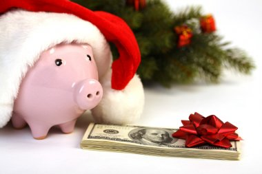 Part of piggy bank with Santa Claus hat and stack of money american hundred dollar bills with red bow and christmas tree standing on white background