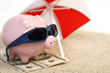 Summer piggy bank standing on towel from greenback hundred dollars with sunglasses on the beach sand unter red and white sunshade