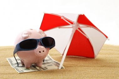 Summer piggy bank standing on towel from greenback hundred dollars with sunglasses on the beach sand under red and white sunshade