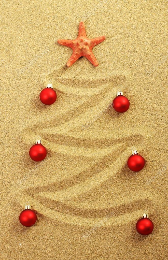 Christmas tree on painting in sand with red starfish and red matt christmas balls