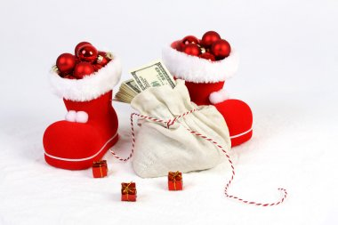 Two Santas boots with red mat christmas balls and Santas bag with stack of money american hundred dollar bills and three gifts with gold bow on snow