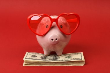 Piggy bank in love with red heart sunglasses standing on stack of money american hundred dollar bills on red background