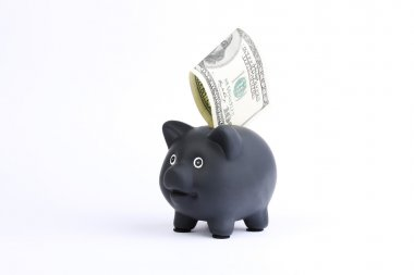 Black piggy bank with one hundred dollars bill falling into slot on a white studio background
