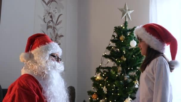 Roztomilá holčička v novoroční čepici mu sundá vousy ze Santa Clause. Vtipné okamžiky na Vánoce a Nový rok.