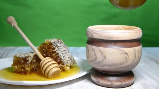 Lití medu ve sklenici na dřevěný stůl a zelené pozadí, hromokey