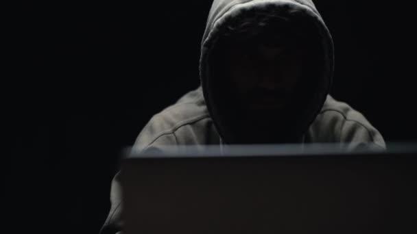 Přední pohled hacker muž hackování on-line webové stránky nebo zapojení hackování do bezpečnostních systémů.