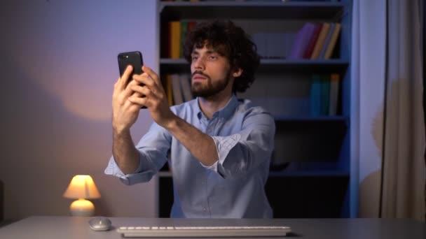POV-Aufnahme eines ernsthaften jungen Mannes, der versucht, Handy-Signal während der Arbeit am Computer zu fangen.