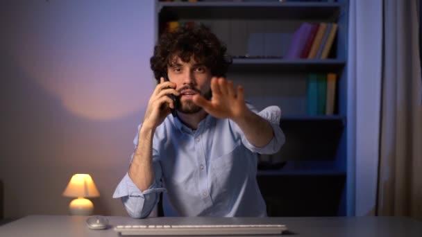 POV-Aufnahme eines geschäftigen Geschäftsmannes, der am Handy spricht, am Computer arbeitet und Handgesten macht.