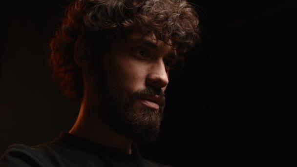 Detailní záběr nízkoúhlého záběru vousatého mladého muže s on-line video hovorem přes notebook v tmavé místnosti.
