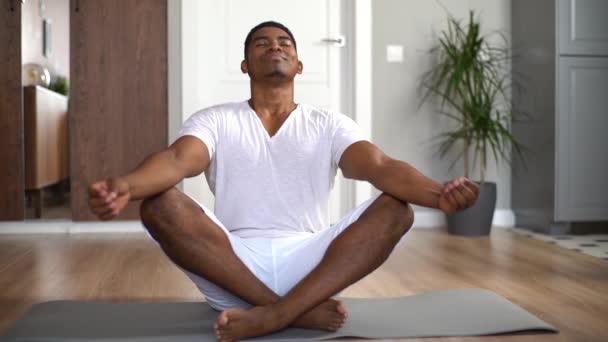 Entspannter afroamerikanischer Mann mit geschlossenen Augen, der zu Hause meditiert und in Lotusposition auf Matte sitzt.