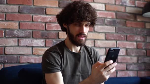 Nahaufnahme eines bärtigen jungen Mannes mit Videoanruf auf dem Handy, der auf der Couch im Wohnzimmer sitzt.