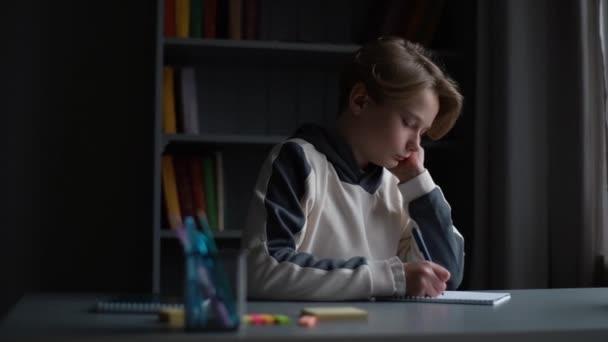 A fókuszált tanuló fiú portréja, amint jegyzetel a másolókönyvben tollal az íróasztalnál a sötét szobában..