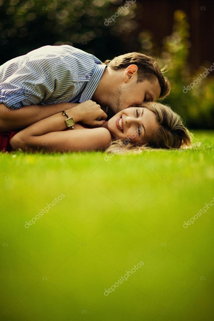 Young beautiful couple lie on the lawn