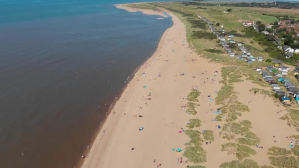 Aerial footage of the British seaside town of Hunstanton Norfolk showing people and families sunbathing and playing on the beach on the south end of the beach.