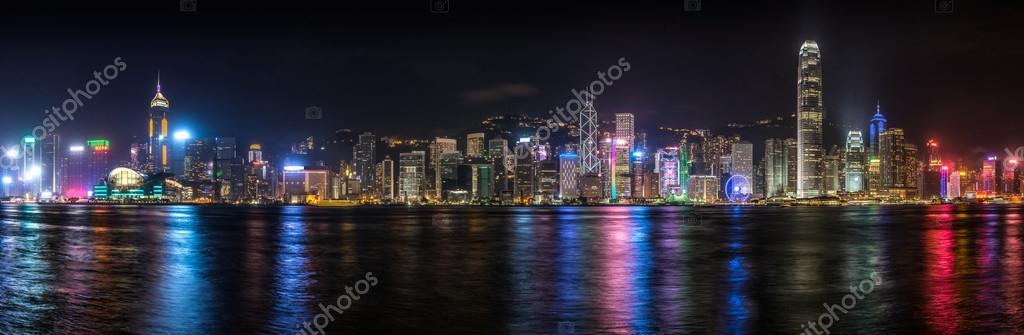 Panorama of the Hong Kong skyline lit up at night along Victoria Harbor.
