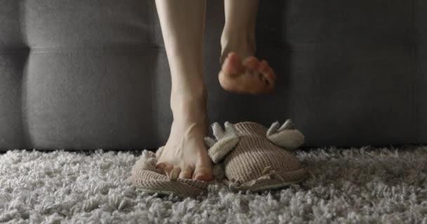 žena sedí na pohovce a sundává si pantofle