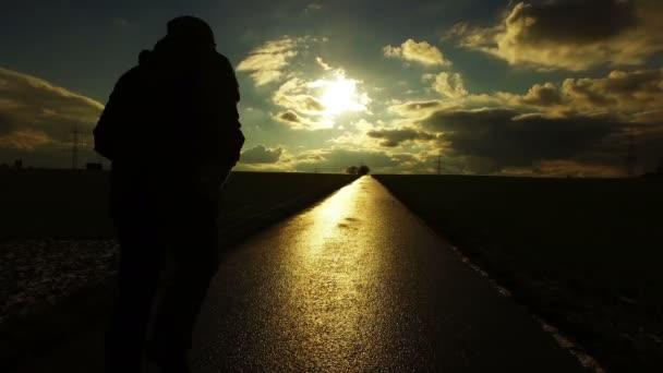 Emberek sziluettje úton mező jellegű naplemente táj