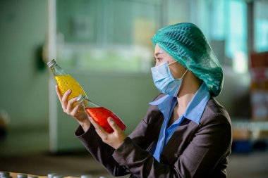 Worker of science in bottle of Basil seed beverage factory wearing safety  hat and face mask working check quality of drink Basil seed produce on conveyer belt before distribution to market business
