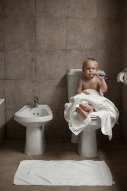 Toddler brushing his teeth after bath