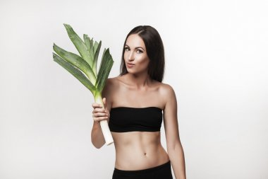 Portrait of young fit woman holding leek