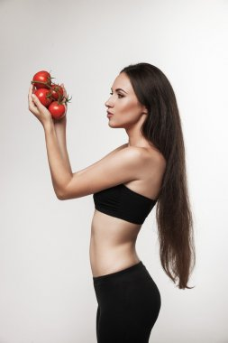 Portrait of young fit woman holding glossy red tomatoes