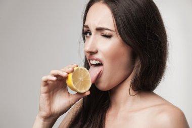 Funny image of young woman eating lemon