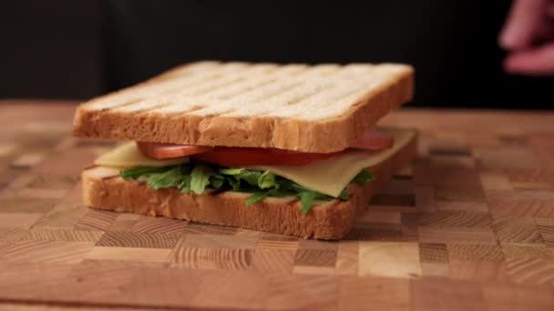 A nő késsel vágja a szendvicset.