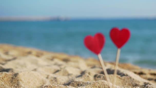krásná červená dřevěná srdce na pozadí moře a oblohy v písku.