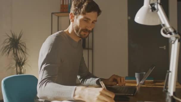 Szakmai Creative Man Ül asztalánál Home Office Studio Dolgozik egy laptop italok ital a kupából, írja le ötleteit jegyzettömbbe. Fényes modern szoba. 360 fokos nyomkövető ívlövés