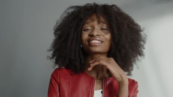 Atraktivní černošky dívka s bujnou kudrnaté vlasy pózování pro módní časopis Photoshoot. Krásná dívka se usmívá hravě a jedná pro focení Made in Professional Studio. Portrétní snímek