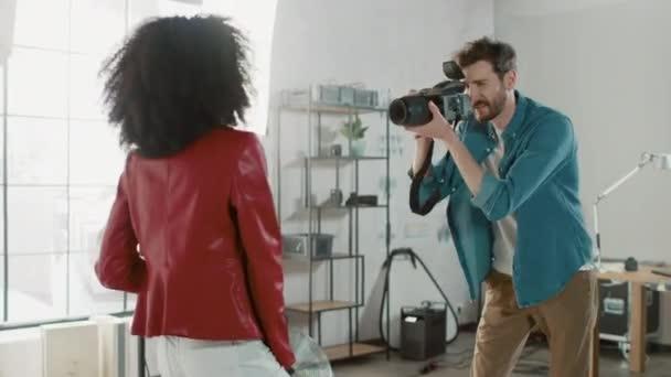 Krásná černá modelka Posing pro fotografa, on fotí s profesionální kamerou. Hraje si s Facial Expressions. Stylový módní časopis focení v ateliéru