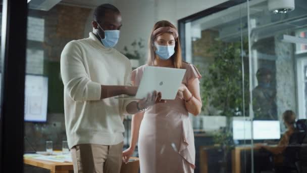 Moderner Bürochef mit Gesichtsmaske im Gespräch