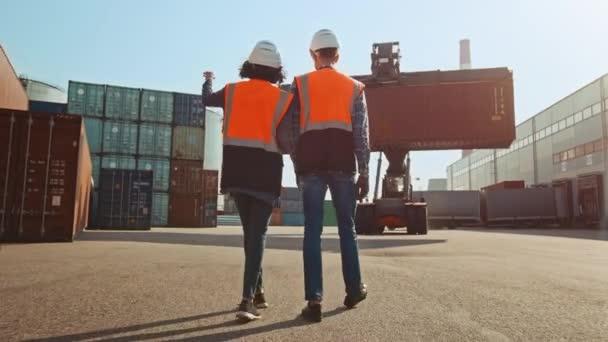 Průmysloví inženýři s tabletem v kontejnerovém terminálu