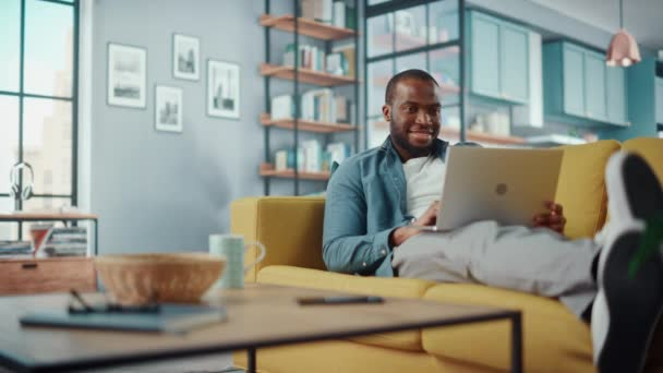 Männchen mit Laptop sitzt im Wohnzimmer