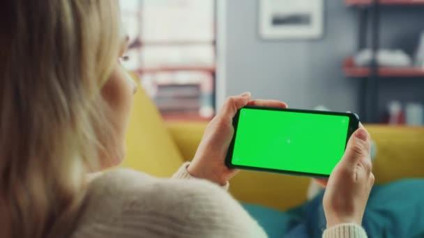 Žena pomocí Smartphone se zelenou obrazovkou v obývacím pokoji