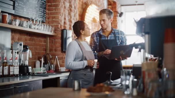 Nő és férfi kávézó tulajdonosok megvitassák a munka Laptop