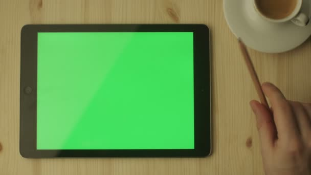 Tablet with Green Screen Laying on a Wooden Table.