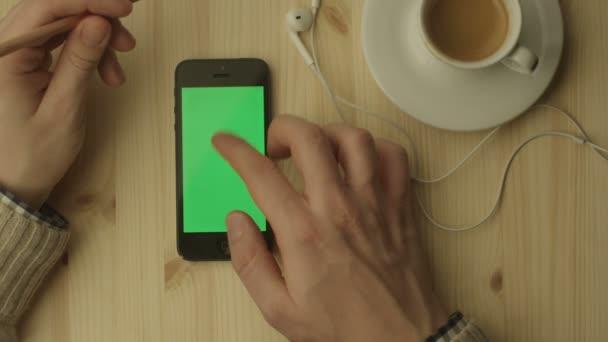 Telefon s zelenou obrazovkou na dřevěný stůl