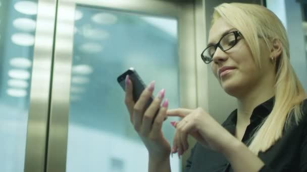 Podnikatelka pomocí mobilního telefonu a úsměv v úřadu výtahu