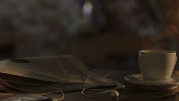 snímek šálek kávy a novin na stole v ranní slunce