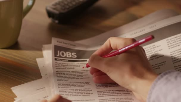 Man Looking for Job in a Newspaper and Marking Advertisement Using Red Pencil